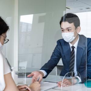 パーティション越しに話すマスクの接客者とお客様