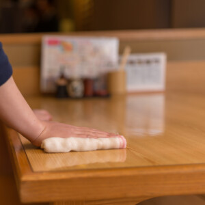 店のテーブルを拭くスタッフ